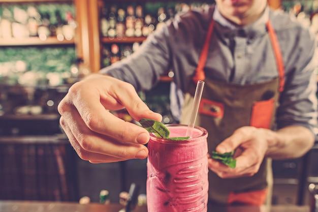 Deskundige barman maakt cocktail in nachtclub.