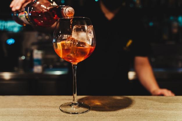 Deskundige barman maakt cocktail in nachtclub