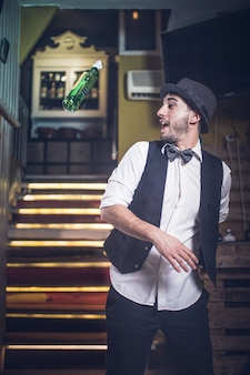 Deskundige barman met hoed en vlinderdas die fles in de lucht werpt
