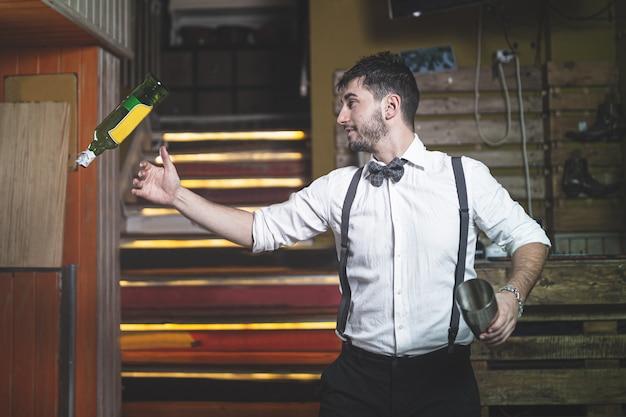 Deskundige barman met vlinderdas die fles in de lucht werpt.