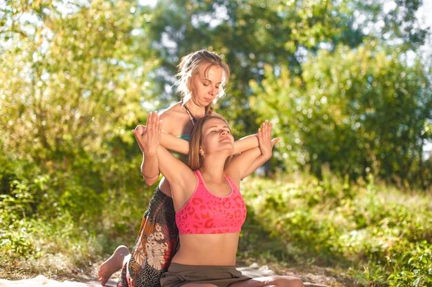 Deskundige masseuse demonstreert verfrissende massagemethoden op het gras van het bos.