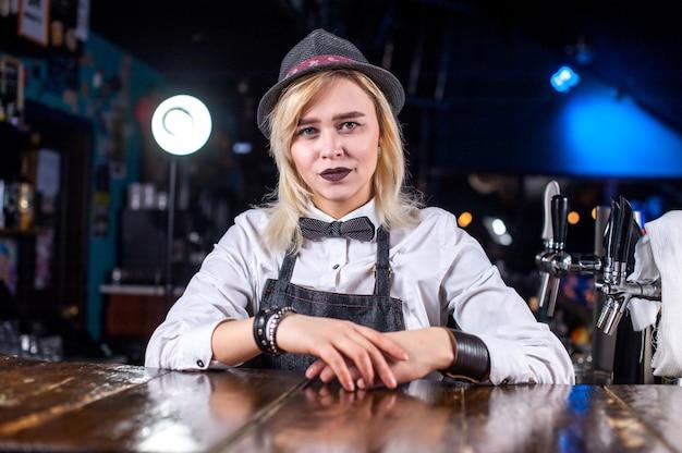 Deskundige meisje barman is een drankje gieten terwijl je in de buurt van de toog in de bar