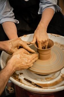 Deskundige pottenbakker leert een vrouw aan het pottenbakkerswiel te werken