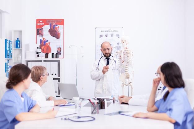 Deskundige radioloog demonstreert op skelet tijdens briefing met medisch personeel in de vergaderruimte van het ziekenhuis. kliniektherapeut in gesprek met collega's over ziekte, medisch professional