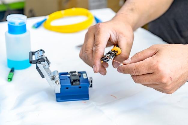 Deskundige technicus striptraad voor te bereiden in de glasvezelkabelkop