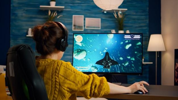 Deskundige vrouw gamer die space shooter-videogame speelt op een krachtige pc. virtueel schietspelkampioenschap in cyberspace, esports-speler presteert op computer in stijlvolle kamer tijdens gametoernooi