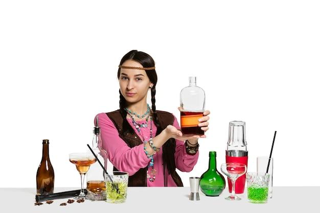 Deskundige vrouwelijke barman maakt cocktail in studio geïsoleerd op een witte muur