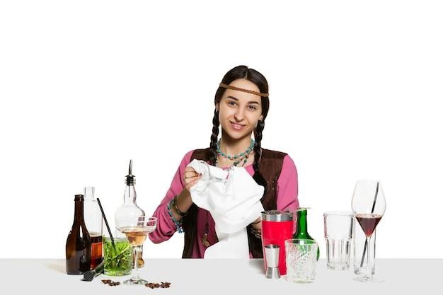 Deskundige vrouwelijke barman maakt cocktail in studio geïsoleerd op wit