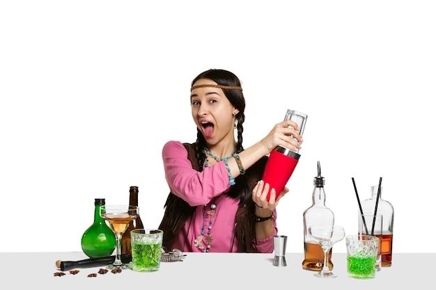 Deskundige vrouwelijke barman maakt cocktail in studio