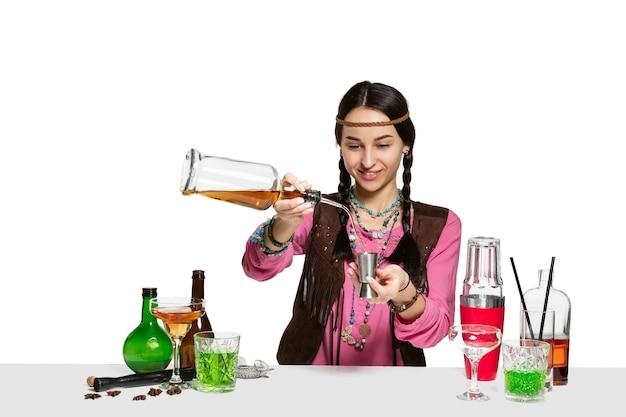 Deskundige vrouwelijke barman maakt cocktail op geïsoleerd op een witte muur. internationale barmandag, bar, alcohol, restaurant, feest, pub, nachtleven, cocktail, nachtclubconcept