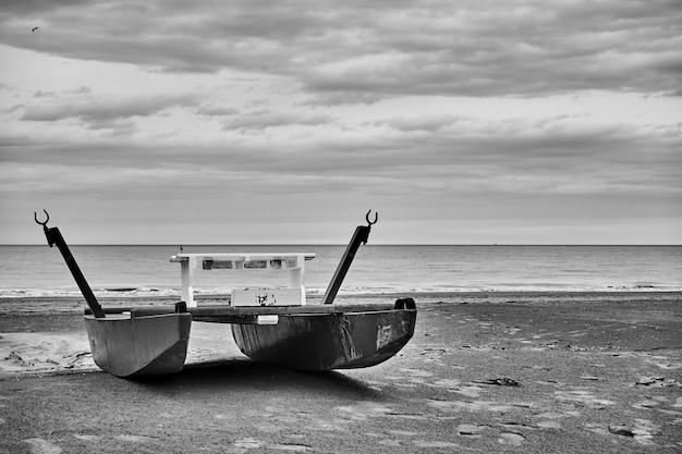 Desolaat strand met badmeesterboot aan zee. zwart-wit fotografie, landschap. rimini, italië