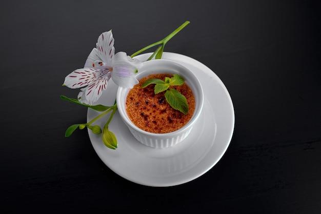 Dessert creme brulee, in een witte schaal met muntblaadjes in witte bloemen, op een donkere achtergrond,