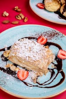 Dessert gegarneerd met suikerpoeder en aardbeien
