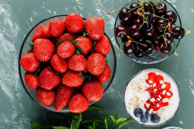 Dessert in een vaas met aardbeien, bosbessen, munt, kersen plat lag op een gips oppervlak