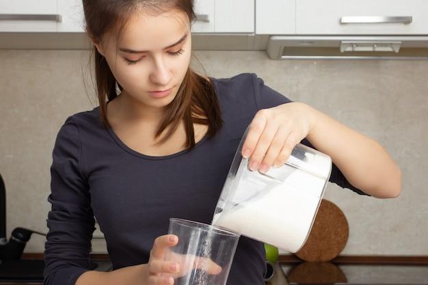 Dessert koken. meisje giet kristalsuiker in een maatbeker in de keuken.