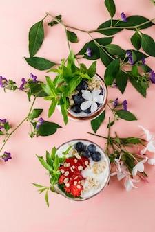 Dessert met aardbeien, bosbessen, noten, munt, bloemtakken in beker en vaas op roze oppervlak, bovenaanzicht.