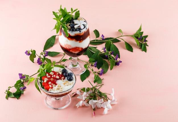 Dessert met aardbeien, bosbessen, noten, munt, bloemtakken in beker en vaas op roze oppervlak, hoge hoek bekeken.