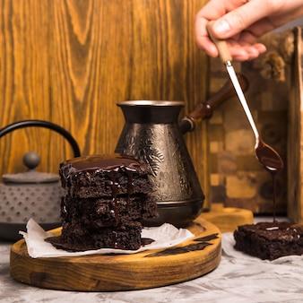Dessert met cacao brownies in chocolade in de buurt van theepot en koffie turk