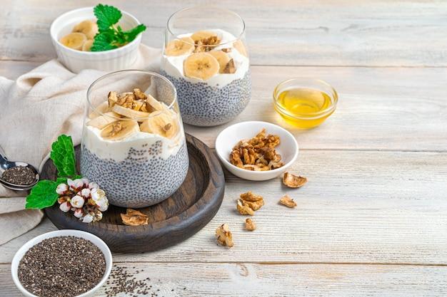 Dessert met chiazaden, plantaardige melk, honing, noten en banaan op een lichte muur met ruimte om te kopiëren. vitaminepudding met calcium en omega 3.
