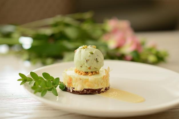 Dessert met een bal van pistacheroomijs met bloemdecor