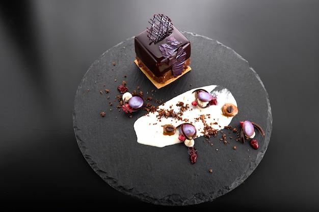 Dessert met noten in chocoladeglazuur in de vorm van een kubus op zwarte leisteen