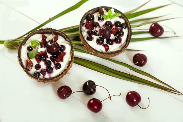 Dessert met slagroom en kersen en aalbessen in kokoskoppen op palmbladeren