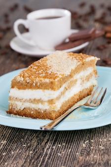 Dessert met veel calorieën, heerlijke cake in stukjes gesneden, meerlaags gebak met botercrème als dessert