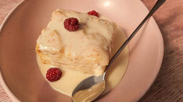 Dessert napoleon met vla, gecondenseerde melksaus, versierd met frambozen. op een houten natuurlijke achtergrond.