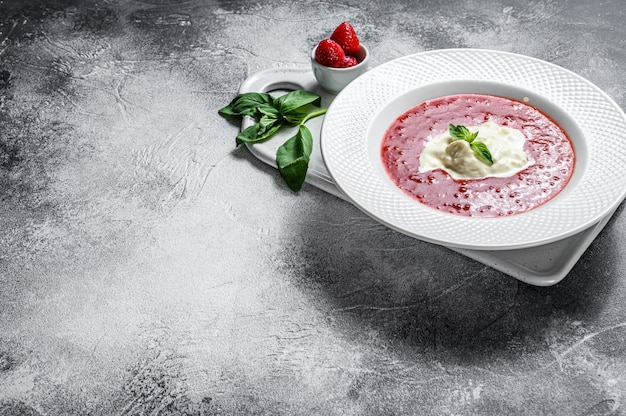 Dessert van aardbeipuree en stracciatella mozzarella. grijze muur. ruimte voor tekst