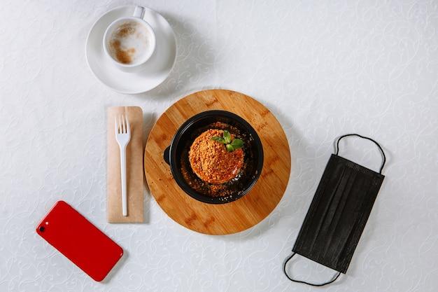 Dessert van de bezorgdienst, liggend op tafel. ernaast is een telefoon en een medisch masker