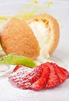 Dessert van ijs op biscuit met aardbei en karamel
