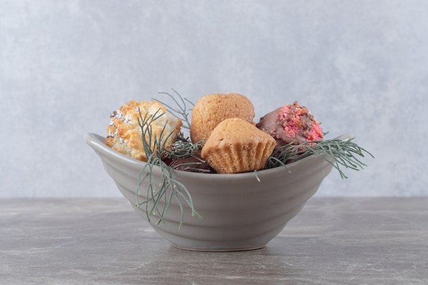 Dessertassortiment op een kleine kom versierd met pijnboombladeren op marmeren oppervlak