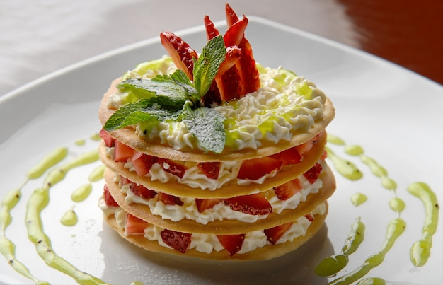 Dessertcake met verse aardbeien met room, munt en jam