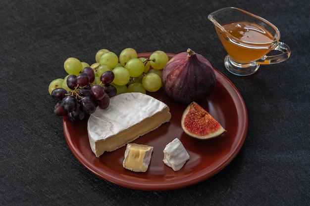 Desserthapjes tot wijn vijgen brie kaas rode en groene druiven honing geserveerd op een keramisch bord op