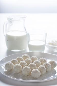 Dessertkokoscake en melk in een kruik op een lichte achtergrond