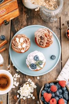 Desserts met room, bosbessen en chocolade. lay-out van desserts met noten op een houten tafel.