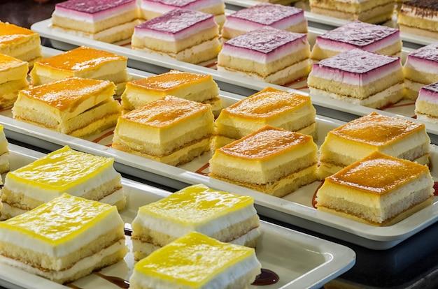 Desserts van smakelijke koekjes van verschillende kleuren en smaken, limoen, aardbei en room op witte rechthoekige avocado.