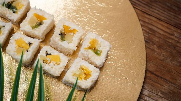 Dessertsushi - roll met verschillende soorten fruit en roomkaas erin. op een gouden achtergrond en met een tropisch blad