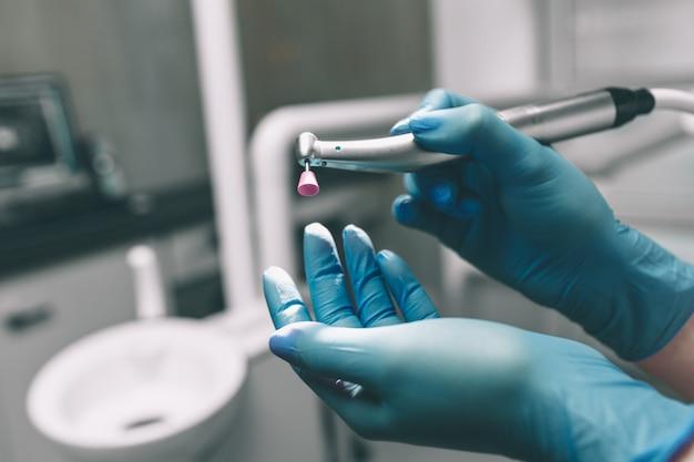 Detail dat van hand tandhulpmiddelen in tandkliniek houdt. tandarts concept.
