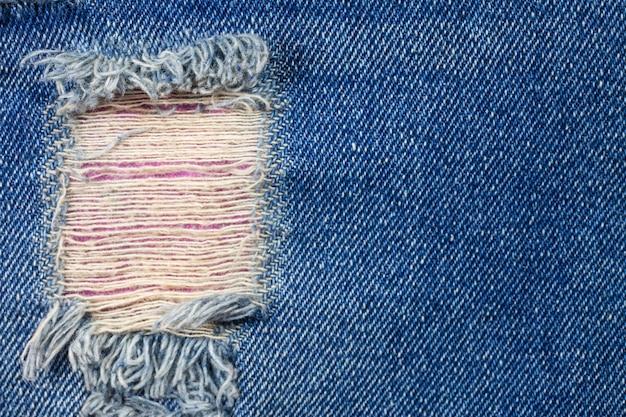 Detail gescheurde oude spijkerbroek achtergrond.