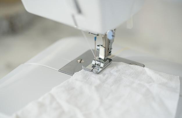 Detail op naaimachine. selectieve aandacht. zelfgemaakte medische masker in proces.
