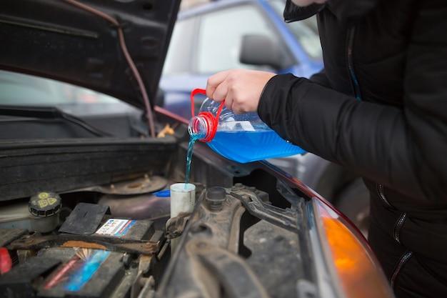 Detail over het gieten van antivries vloeibare ruitensproeiervloeistof in vuile auto van blauwe en rode antivrieswatercontainer, autoconcept