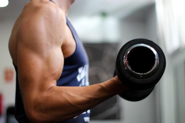 Detail van de arm van een man die bicepsoefeningen uitvoert in de sportschool
