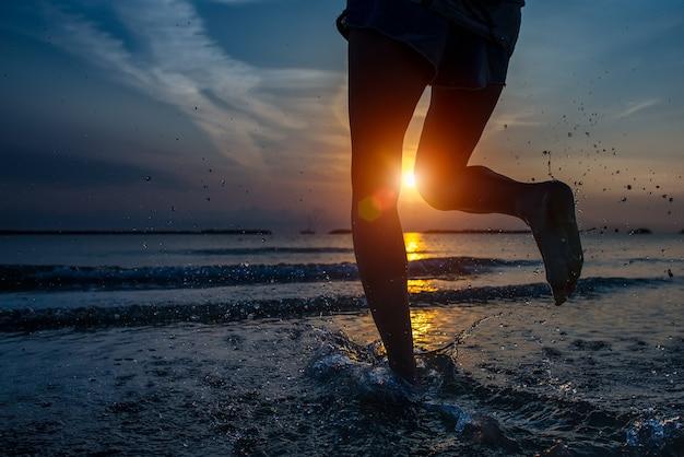 Detail van de benen van de vrouw lopen door de zee