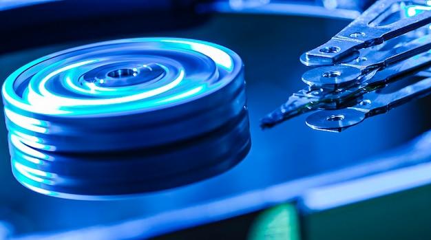 Detail van de binnenkant van een harde schijf met de leeskop in werking, blauw licht afbeelding