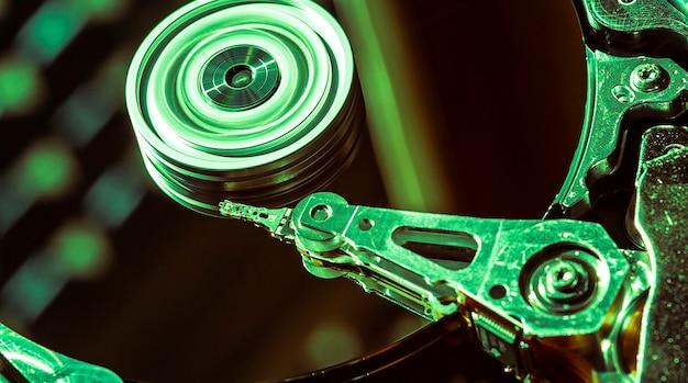 Detail van de binnenkant van een harde schijf met de leeskop in werking, groen licht afbeelding