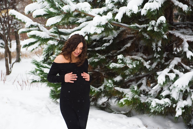 Detail van de buik van de onherkenbare zwangere vrouw in de winter.