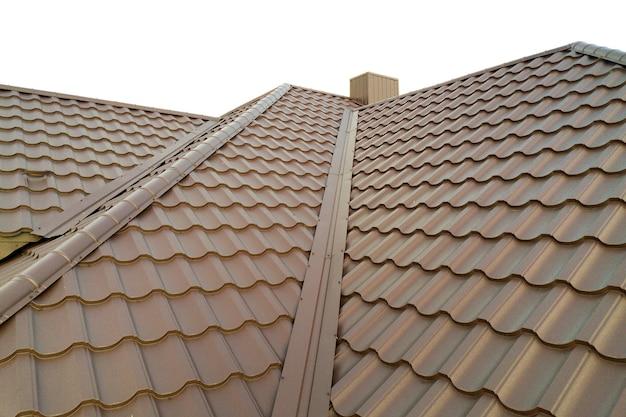 Detail van de dakconstructie van het huis bedekt met bruine metalen tegelplaten.