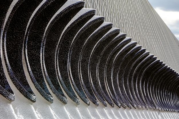 Detail van de gevel van een gebouw met eivormige geometrische vormen.