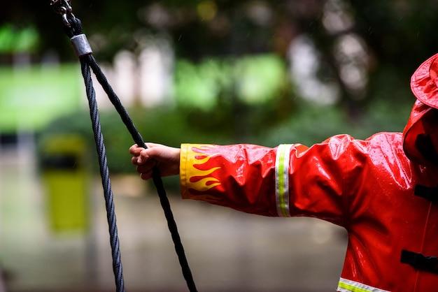 Detail van de hand van een kindbrandweerman met zijn arm uitgestrekt, vastgebonden aan een touw tijdens een regenachtige dag.